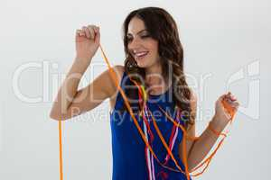 Woman wrapped in multi color streamers posing against white background