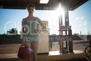 Woman holding a petrol can at petrol pump