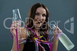 Smiling woman wrapped in multi color streamers holding champagne bottle and glass