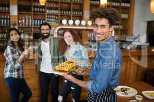 Smiling waiter serving tray of baby corn to customers