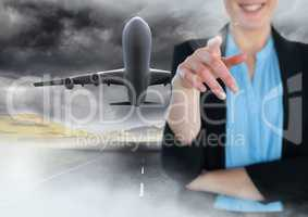 Businesswoman touching air in front of flying plane on runway