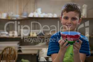 Boy holding a panted pot in pottery workshop