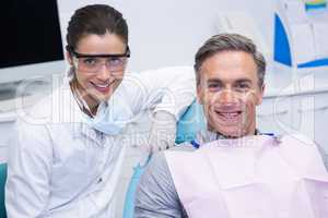 Smiling dentist by patient at medical clinic