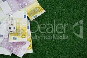 Footballs and currency notes on artificial grass