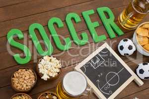 Strategy board, snacks and football on wooden table