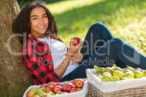 Mixed Race African American Girl Teenager Eating Apple by Tree