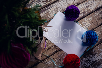 Christmas decoration and blank paper on wooden plank
