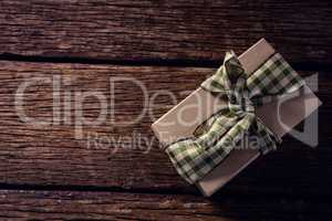 Wrapped gift box on wooden plank