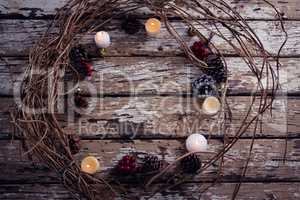 Lit candles and christmas decoration on wooden plank