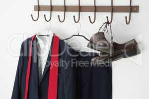 Close-up of full suit and shoes hanging on hook