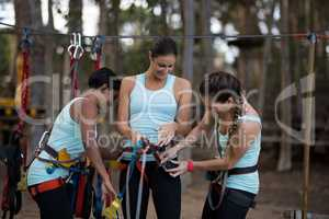 Female friends getting their belt tied to perform zip line