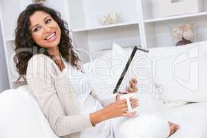 Woman Laughing Drinking Tea or Coffee Using Tablet Computer