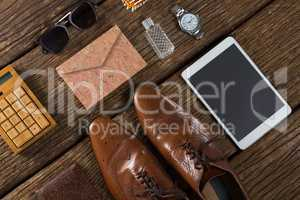 Shoes, digital tablet and sunglasses on wooden plank