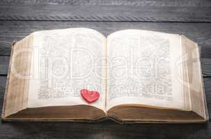 Red heart on an antique book