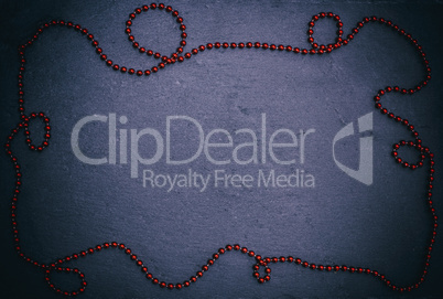 black background with red Christmas garland of small balls
