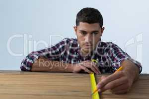 Male architect measuring wooden plank with tape measure
