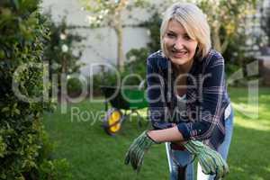 Beautiful woman leaning on gardening equipment