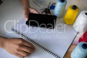 Fashion designer using mobile phone at desk