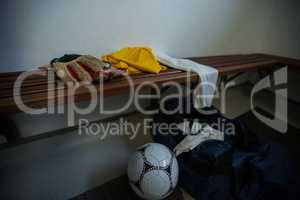 Gloves with football jersey, soccer ball and travel bag on bench
