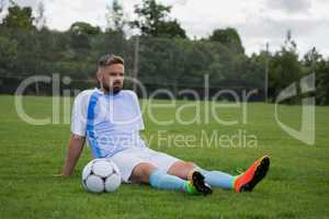 Football player relaxing in the ground