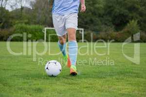 Football player dribbling the soccer