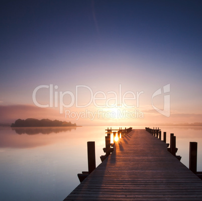 boardwalk leads out onto the lake, silent at lake while sunrise