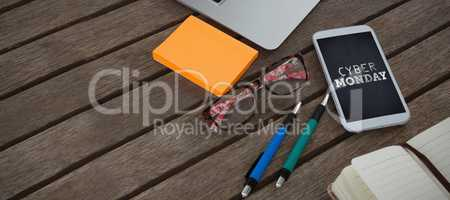 Composite image of mobile phone, laptop, pen, sticky note, spectacles and organizer on wooden plank