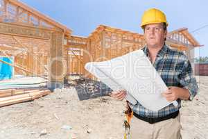 Male Contractor With House Plans Wearing Hard Hat In Front of Ne
