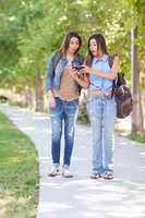 Two Beautiful Young Ethnic Twin Sisters With Backpacks Using A S
