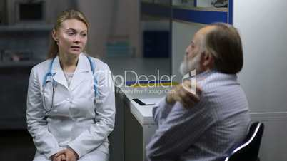 Elderly man consulting with neurologist in clinic