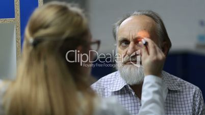 Doctor checking eye symptomatology with flashlight