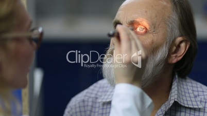 Physician examining pupillary reflex with flashlight