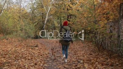 Joyful girl with dog running in autumn park