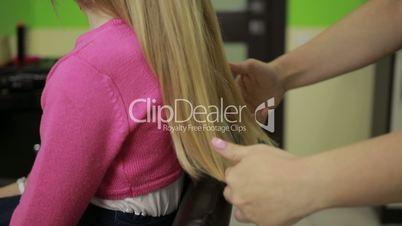 Professional hairstylist arranging child's hair