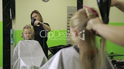 Hairdresser drying girl's hair using blowing dryer