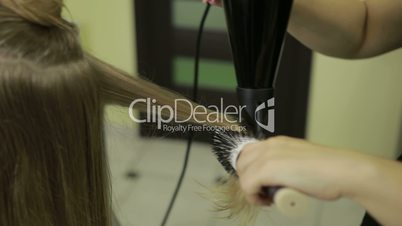Hairstylist drying client's hair in beauty salon