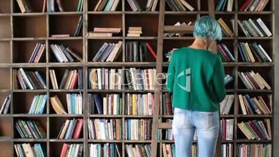Smart girl selecting literature book in store