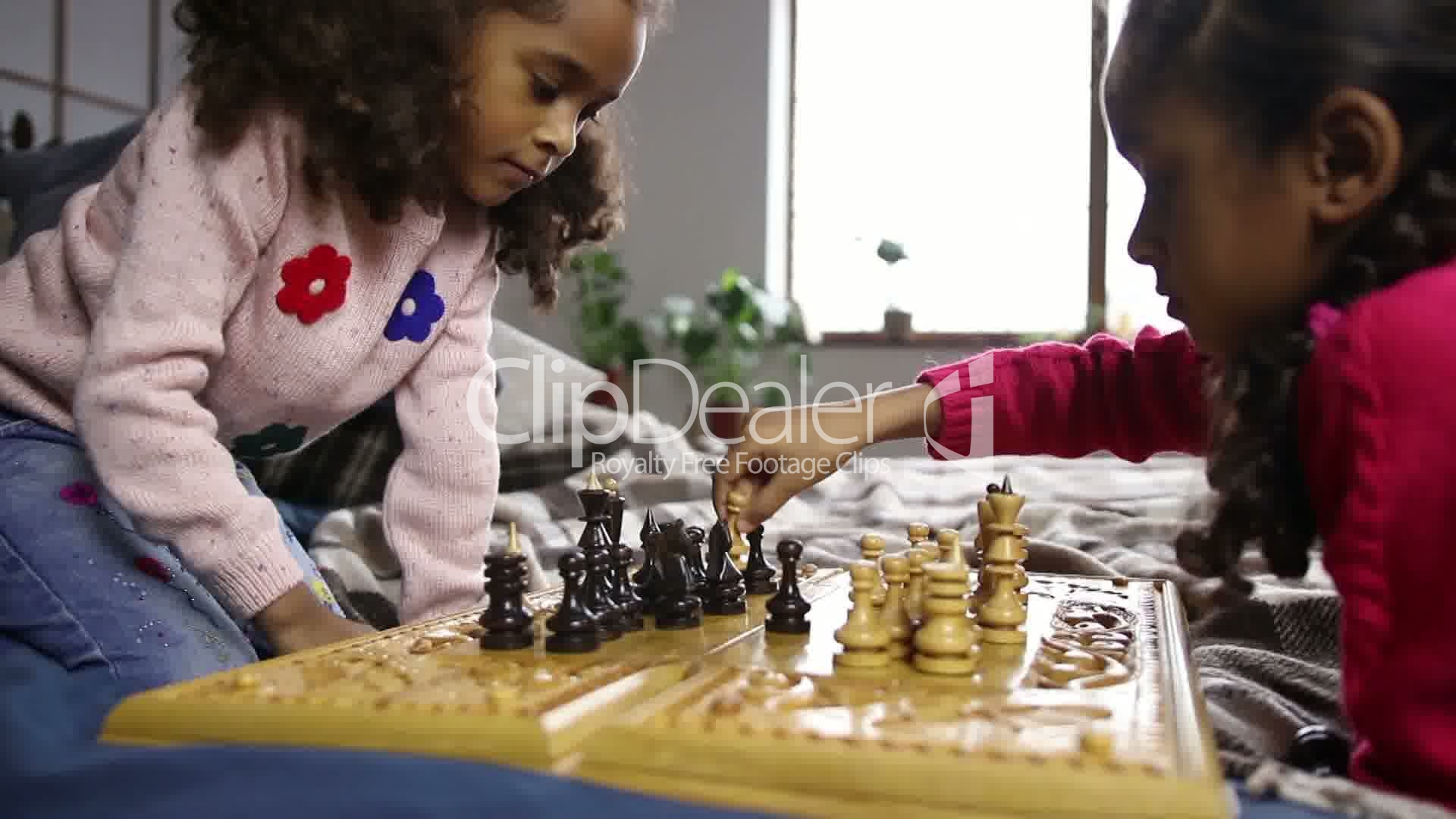 Two smart little girls playing chess on bed: Royalty-free