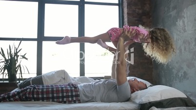Happy father letting his daughter fly in bedroom