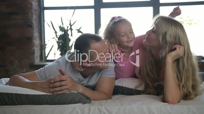 Attractive young family with daughter in bedroom