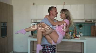 Romantic man carrying wife in his arms at home