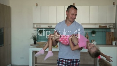 Devoted father spinning daughter in circle at home