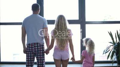 Family with daughter holding hands by the window