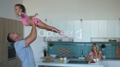 Affectionate dad raising daughter up in the kitchen