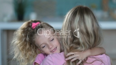 Cute daughter embracing mother with love at home