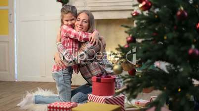 Loving daughter embracing mother on Christmas eve