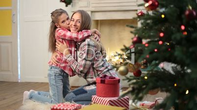 Loving daughter kissing and embracing her mother