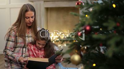 Mother reading book to daughter near xmas tree.