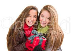 Mixed Race Young Adult Females Holding A Christmas Gift Isolated