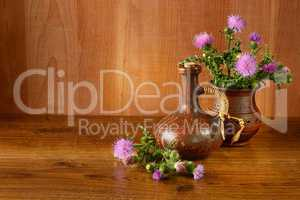Oil and flower of milk thistle on wooden background.